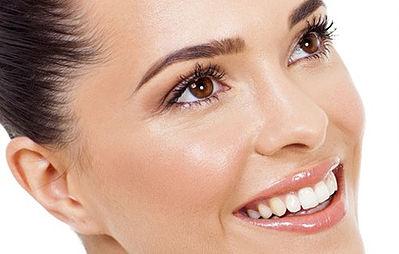 Le visage d'une femme aux cheveux brun souriante.